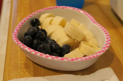 Blueberries and a banana, sliced, in a bowl.