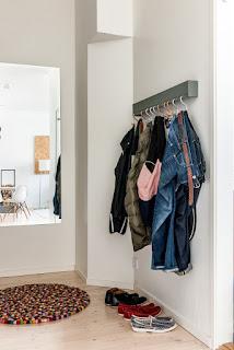 Hall con colgador de metal, espejo y alfombra de bolas
