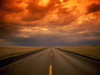 Road going into distance, red clouds