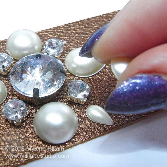 Attaching the pearls and rhinestones to the cuff with adhesive.
