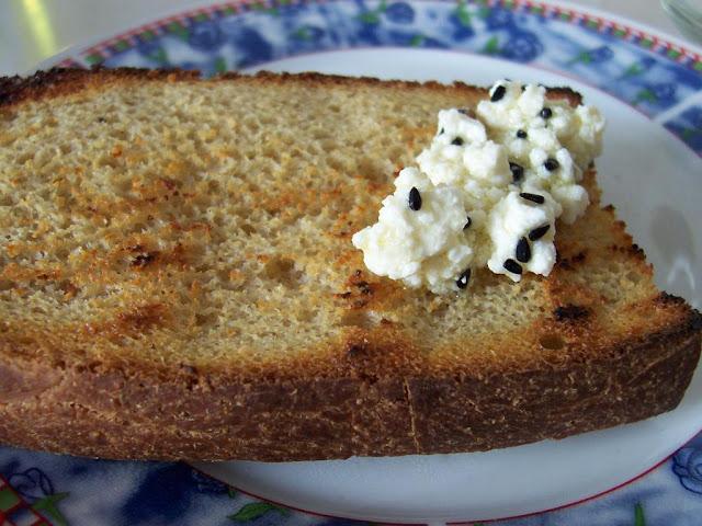 Kızarmış nohut mayalı ekmek dilimi üzerinde karacaotlu peynir