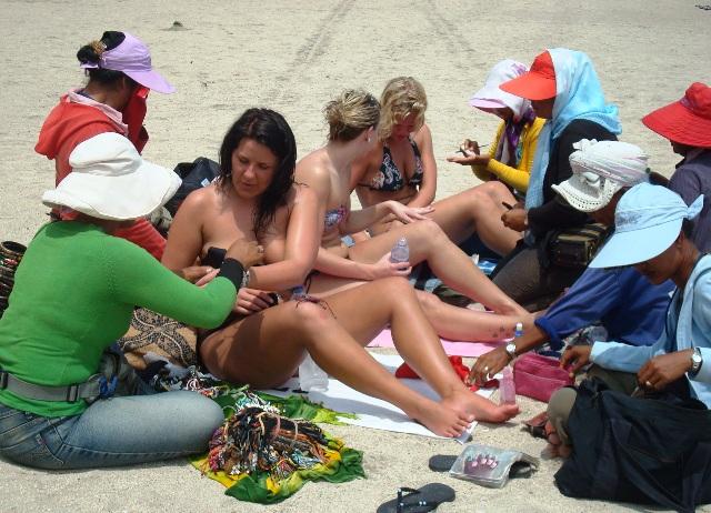suasana para gadis bule berbikini yang sedang berjemur di pantai kuta sedang pijat oleh para tukang pijat yang banyak dikawasan pantai kuta