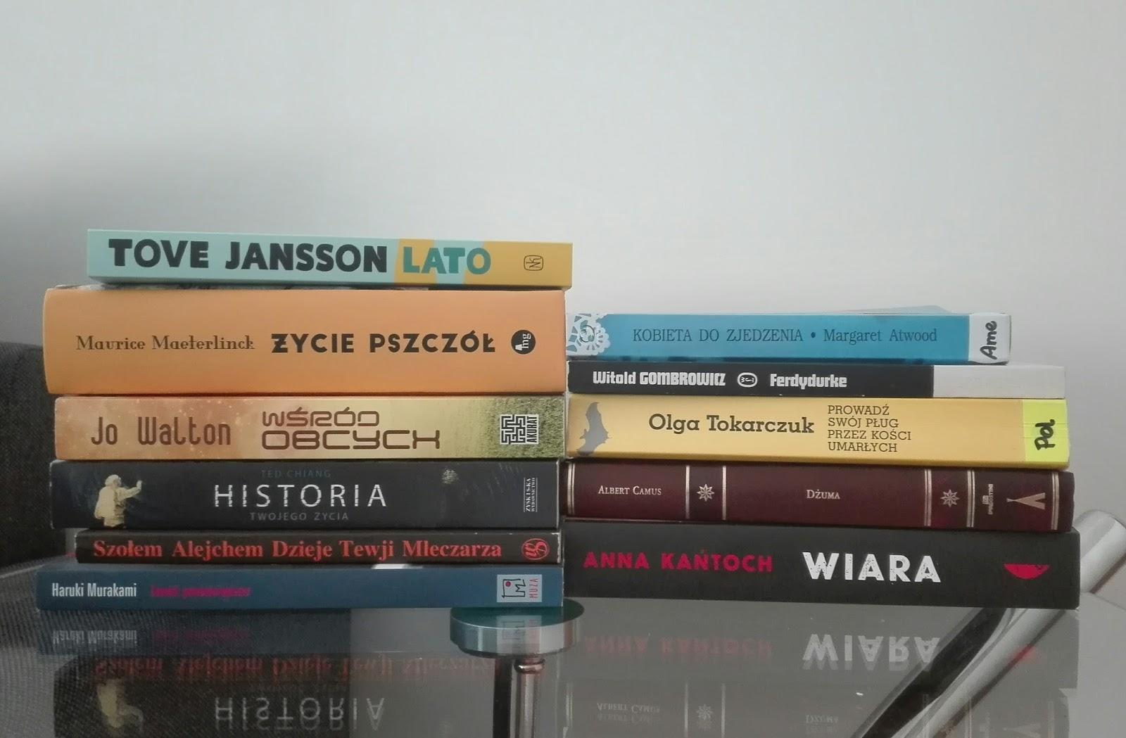 Dwa stosiki książek na stole.