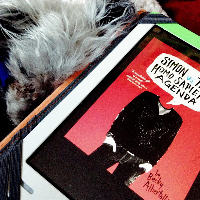 Murchie nestles close against a white Kobo with the red cover of Simon Versus the Homo Sapiens Agenda on it. The illustration features a black-clad boy, hands in pockets, a speech bubble with the book's title on it where his head should be.