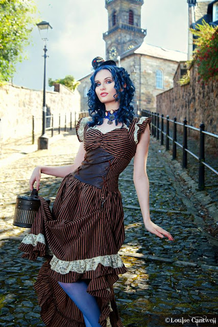 Woman wearing Steampunk clothing in brown and blue. Black and brown striped dress, blue stockings/tights/nylons, hat fascinator, train case purse. Blue hair with spiral curls. Women's Steampunk fashion.