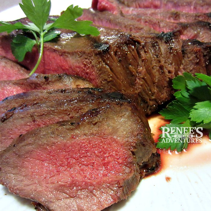 Killer London Broil by Renee's Kitchen Adventures sliced thinly and cooked to medium rare, garnished with fresh parsley
