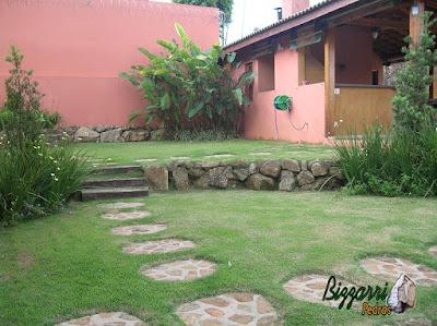 Tipo de muro de pedra no jardim com pedras rústicas assentada sem cimento com os caminhos de pedra com pedras rústicas e a execução do paisagismo em residência em Mairiporã-SP.