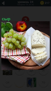 На столе лежат сыр, гроздь винограда, салфетка и яблоко