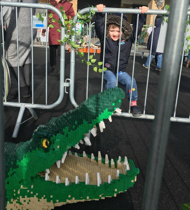 boy-hanging-from-crowd-control-railngs-and-head-of-crocodile-with-mouth-wide-open-teeth-showing--made-from-LEGO-bricks-Cardiff-Bay