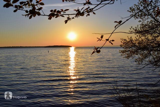 Es wird Abend. Von einem verstecktem Deck aus hinter dem Hafen hat man einen schoenen Blick ueber das Wasser auf die untergehende Sonne.