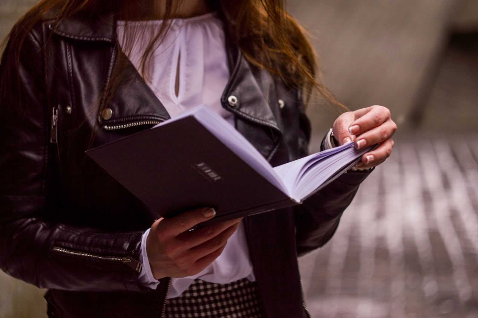 girl in a leather jacket revising from a book