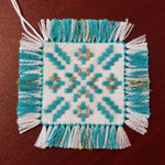 small square turquoise blue and gold geometric embroidery on a white background