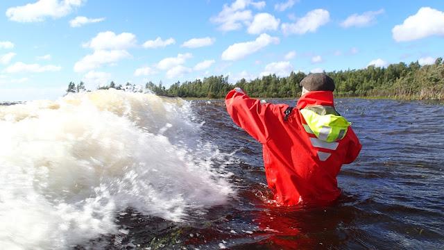 Aalto lyö pelastautumispukuista henkilöä kohti