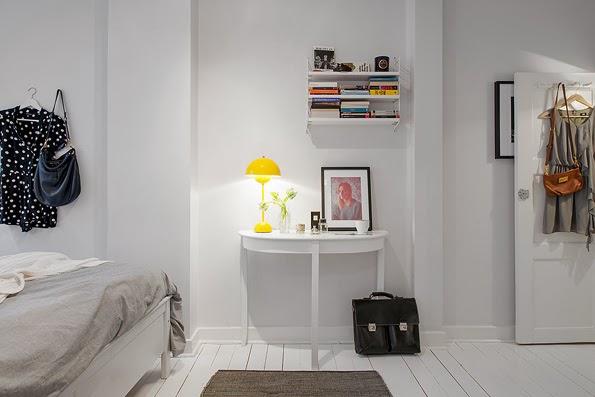 Detalle lámpara color amarillo sobre mesa blanca.