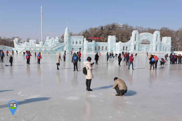Visitors enjoy walking, playing with their top spins and cycling on the frozen lake at Harbin Snow Sculpture Art Expo in Heilongjiang province, China