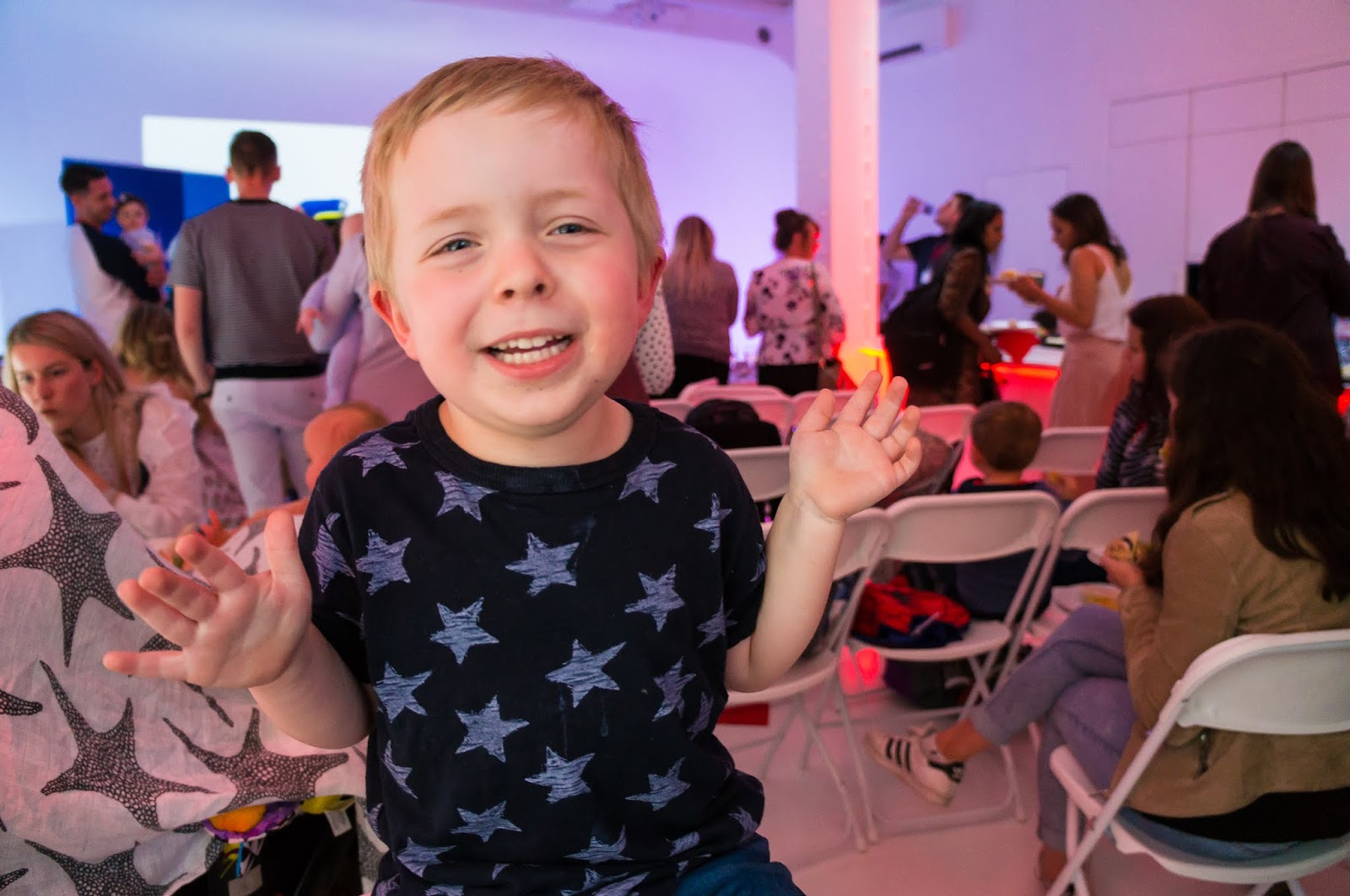 happy child in navy star tshirt waving both hands at nuby big reveal event