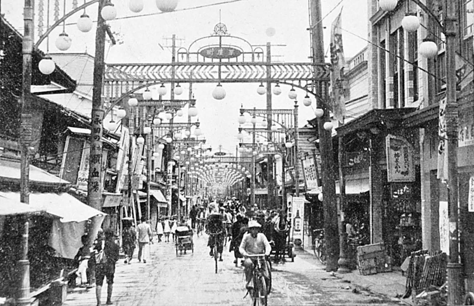 A pre-war photograph of Hiroshima's vibrant downtown shopping district near the center of town, facing east. Only rubble and a few utility poles remained after the nuclear explosion and resultant fires.