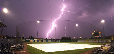 photo of a softball field with lightning in the background