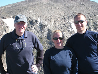 2 men and a woman standing on a mountain