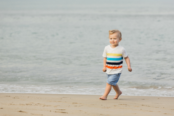 Toddler running on the sand in Hanalei Bay, Kauai