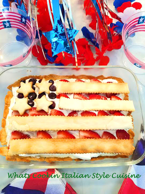 This is a flag shaped cheese pie in a rectangular glass pan with whipped cream, blueberries, sliced strawberries and baked pie crust to make this creative pattern for the 4th of July
