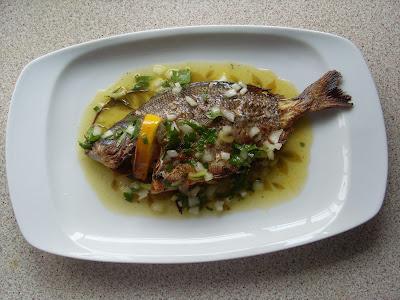 Ψητό ψάρι σε ωραία πιατέλα και απο πανω εχει λαδολέμονο με μαιτανο και κρεμμύδι ψιλοκομένο για γέυση ,επίσης στα βράγχια του έχει μια φέτα λεμόνι