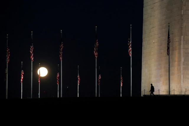 Một người đàn ông đang bước đi qua khu vực công viên National Mall ở thủ đô Washington, Hoa Kỳ bên dưới ánh sáng của Mặt Trăng. Hình ảnh: Carlos Barria/Reuters.