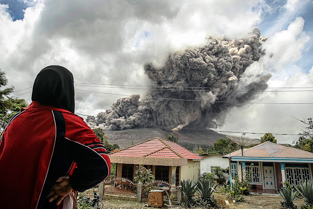 A woman in a village in Karo district in Indonesia's North Sumatra province watches Mount Sinabung erupt