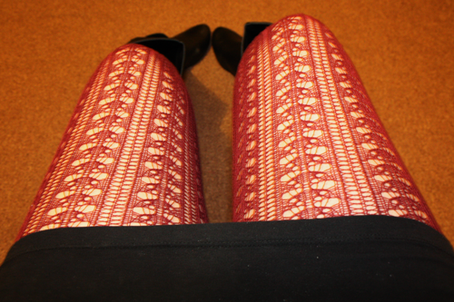a close up of burgundy knitted tights, with a black bodycon skirt and black boots