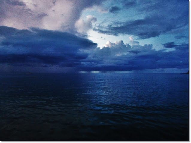 Dark and stormy ocean horizon, with rainfall.