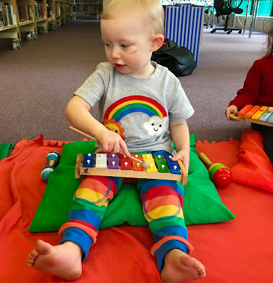A toddler wearing rainbow coloured trousers and a grey t-shirt with a rainbow on