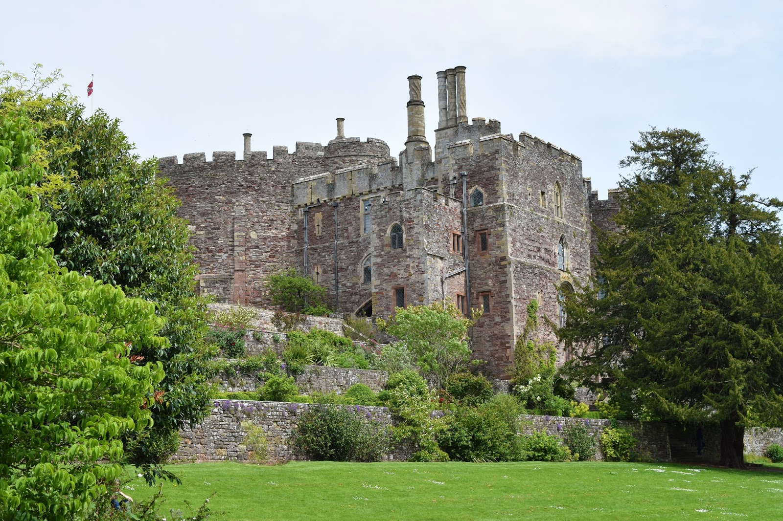looking up towards berkeley castle which is mostly visible apart from the edges which are covered by the trees