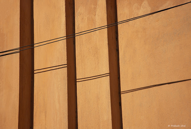 A Minimal Art Photo of a Black Wire running across Diagonally against an Orange textured wall with Vertical Sections.