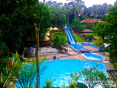 Full photo of the mountain resort with main swimming pool, slide and garden