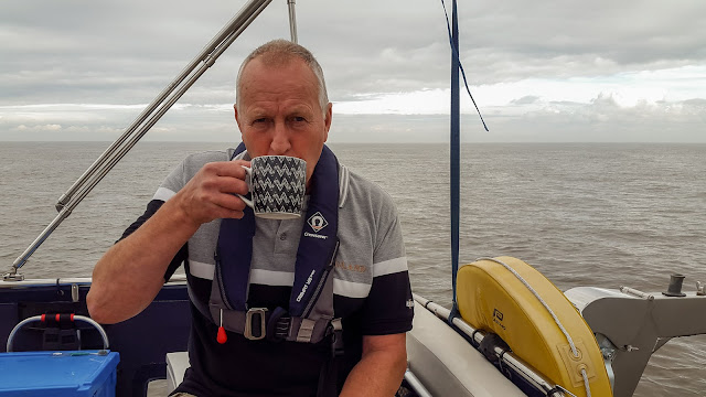 Photo of Phil enjoying his first cup of tea at sea on the aft deck
