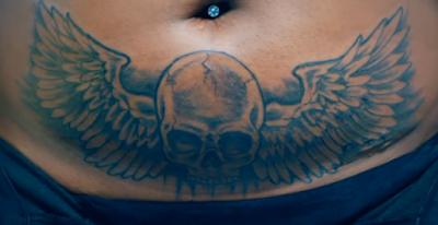 Tatuaje de calavera con alas debajo del ombligo