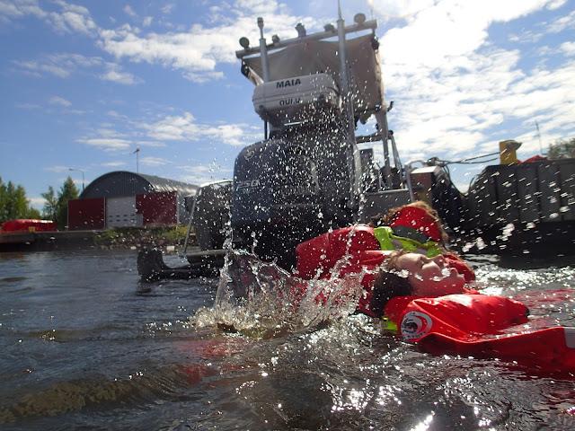 Pelastautumispukuisia ihmisiä pärskii vettä satama-altaassa veneen vieressä