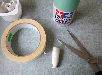 Container of dolls' house miniature white vases, a roll of masking tape, a pair of scissors and a can of spray paint arranged on a piece of baking paper.