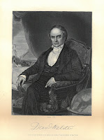 Daniel Webster sitting in a chair with his legs crossed, looking at the viewer. There is a large globe in front of him to his left and over his right shoulder is a writing desk with a pen and other accessories on it.