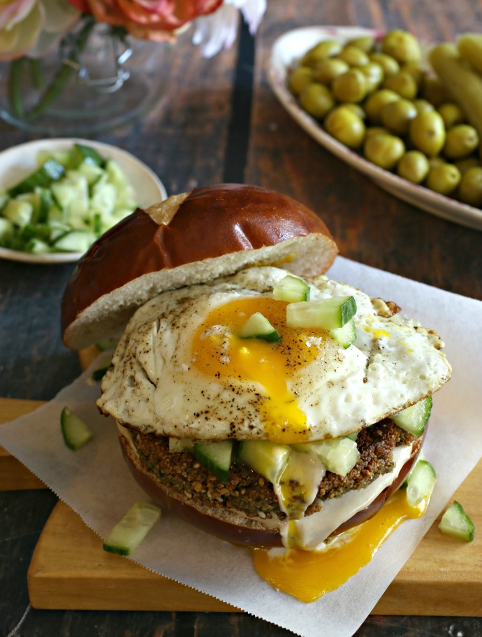 Breakfast sandwich with a falafel patty, tahini, diced cucumbers and topped with a fried egg.