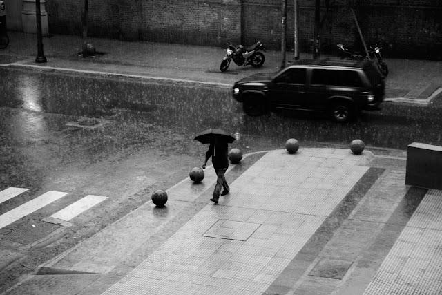 Un hombre bajo un paraguas en plena lluvia,en Blanco y Negro.