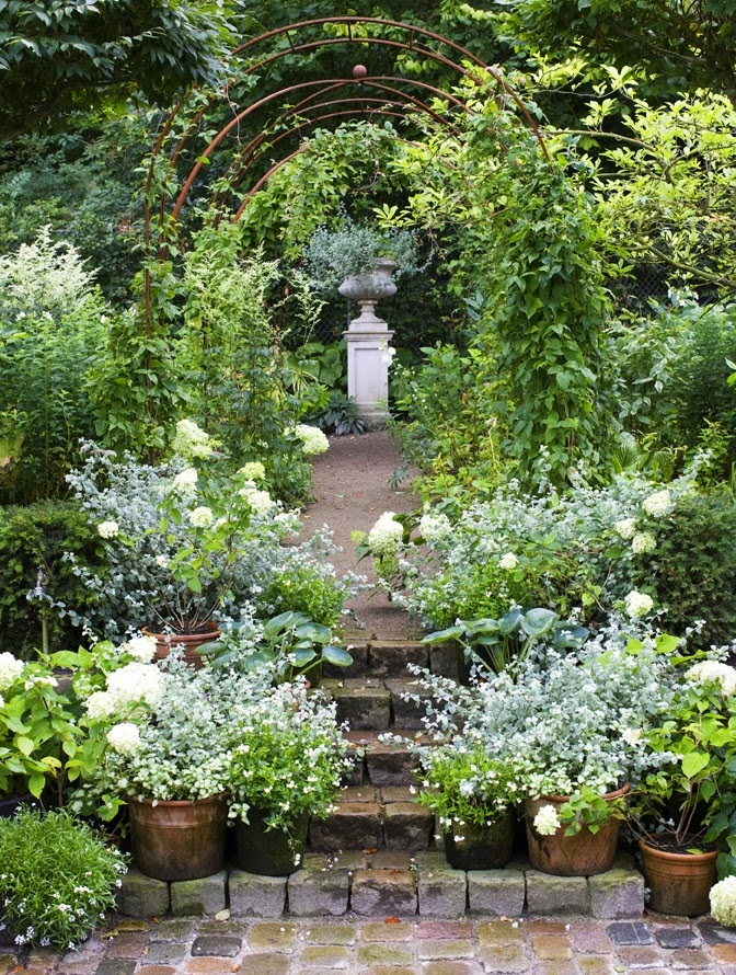 a primeval garden path with visually stunning white on white ending with a white stone planter