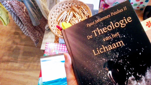 Boek 'De Theologie van het Lichaam' met op de achtergrond een wasrek vol was en een mandje houten wasknijpers.