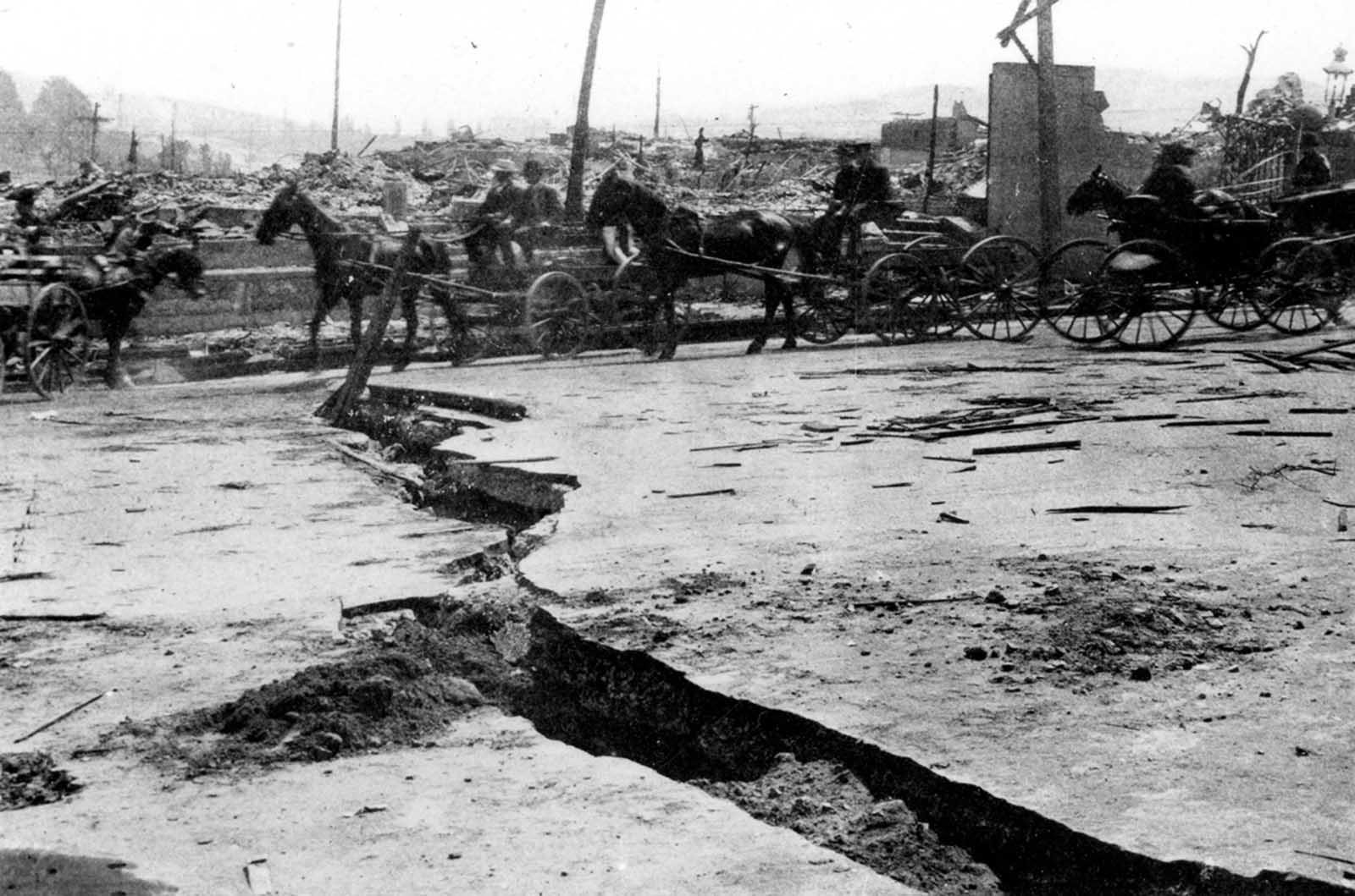 "Disruption of Van Ness Avenue over a filled-in ravine. Original caption: ""Break in asphalt paving on Van Ness Avenue near Vallejo Street. View shows horse-drawn wagon and buggy traffic."""