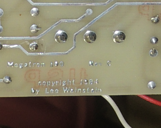 "Extreme close up of circuit board with text ""Megatron 100  Rev. C copyright 1984 by Lee Weinstein"" appearing in solder-coated copper"