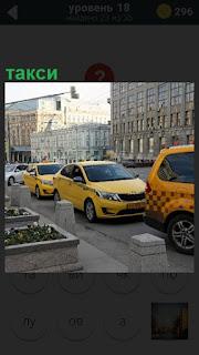 На улицах города стоят желтые такси в ожидании пассажиров