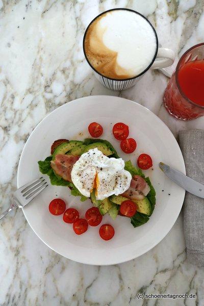 Frühstück: Pochiertes Ei auf geröstetem Brot mit Salat, Avocado, Bacon und Kirschtomaten