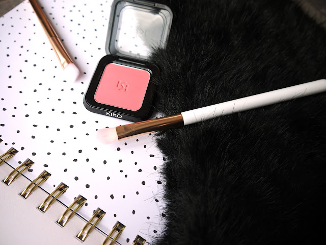 square pan of pink eyeshadow and two makeup brushes on a white background with black polka dots