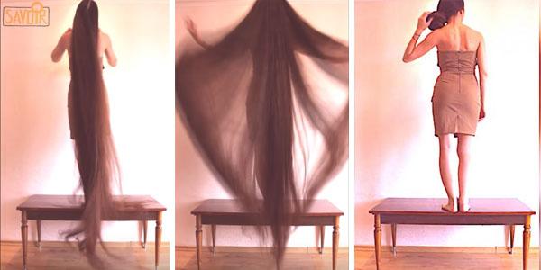 Cette femme est installée sur une petite table. puis, elle pose ses mains sur son chignon. Maintenant, gardez bien les yeux sur ses cheveux!