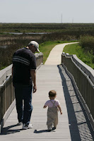 https://upload.wikimedia.org/wikipedia/commons/7/76/A_man_and_toddler_take_a_leisurely_walk_on_a_boardwalk.jpg